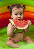 Baby girl in eating watermelon