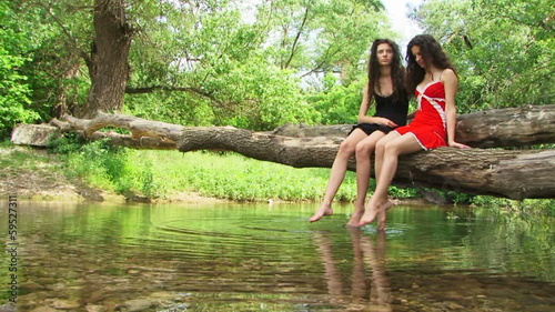 Sisters sitting on a riverside and splashing