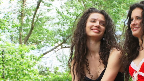 Two beautiful sisters talking and laughing in a forest