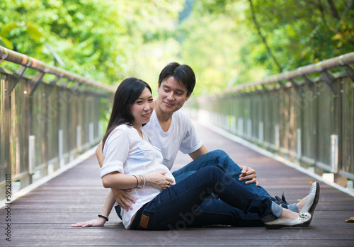 Happy young pregnant asian couple in the nature