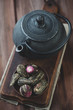 Green tea balls and cast-iron teapot on a wooden surface