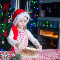 Little cute girl in Santa hat bake gingerbread cookies for