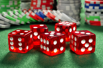 Red dice and chips on a green felt