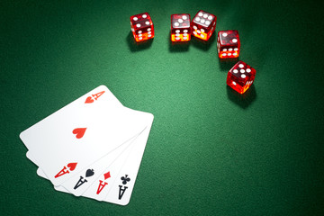 Red dice, four aces  on a green felt