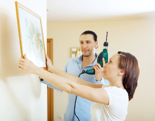 man and woman  hanging   picture  at home