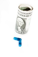 blue pills in front of rolled up dollars on white background