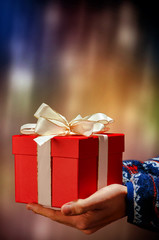 zwei Hände halten ein rotes Geschenk mit weißer Schleife
