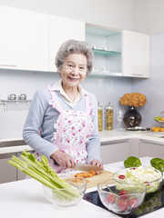 senior woman preparing meal in kitchen