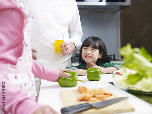 cute little girl talking to parents in kitchen