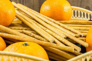 breadsticks and mandarins on wooden background