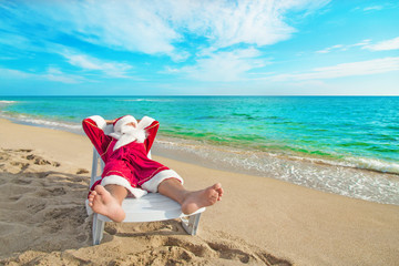 sunbathing Santa Claus relaxing in bedstone on beach - Christmas