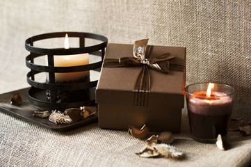 Golden-brown gift box with candles on wooden plate. Burlap/sack