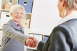 Seniorin begrüßt Beraterin im Büro
