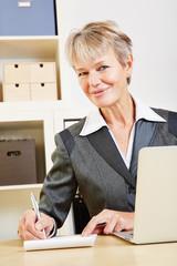 Lächelnde Geschäftsfrau schreibt mit Stift