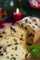 Sliced fruitcake with raisins and mint leaf on christmas backgro