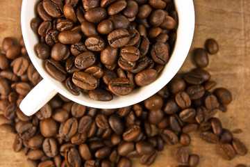 Coffee cup filled with coffee beans on wooden background