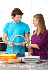Young man helping his wife in household