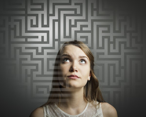 Maze. Girl in white solving a problem.