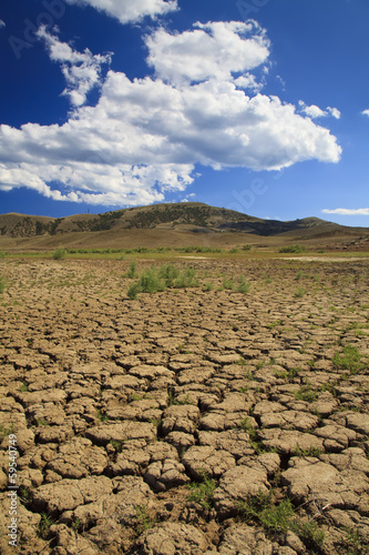 Foto op Plexiglas Droogte Cracked earth under blue sky