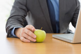 Smartly dressed businessman with laptop and apple at office
