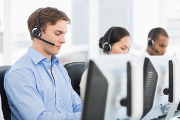 Business colleagues with headsets using computers in office