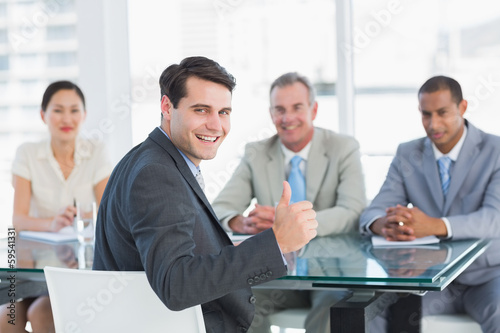 Executive gesturing thumbs up with recruiters during job intervi