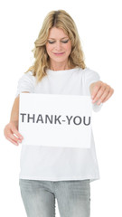 Smiling female volunteer holding 'thank you' paper