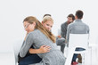 Group therapy session with therapist and client hugging