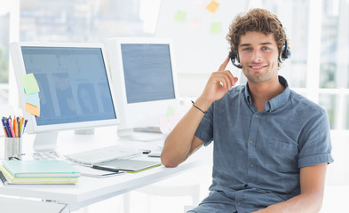 Casual man with headset sitting by computers in office