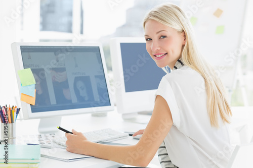 Casual young woman using computer in office