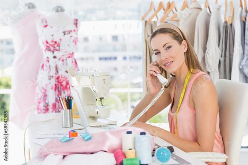 Female fashion designer using phone in studio