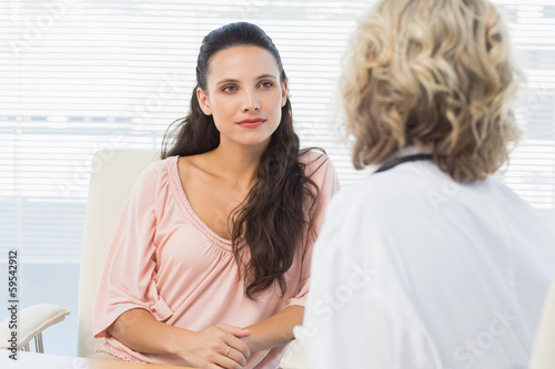 Female patient listening to doctor with concentration in medical