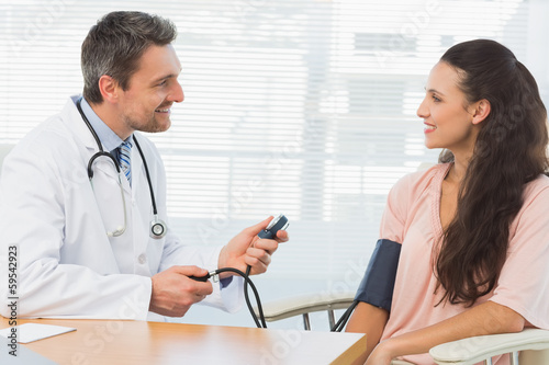 Male doctor checking blood pressure of a young woman