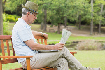 Relaxed senior man reading newspaper at the park