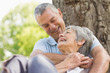 Senior man embracing woman from behind at park