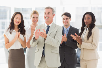 Business team standing and clapping