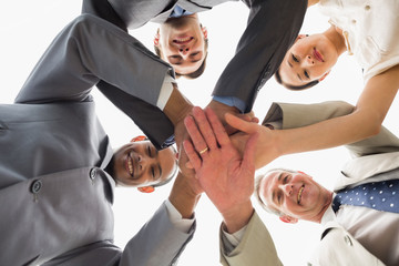 Business team looking down at the camera with hands together