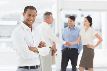 Young businessman with team behind him smiling at camera