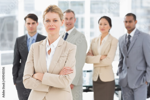 Businesswoman looking at camera with team behind her