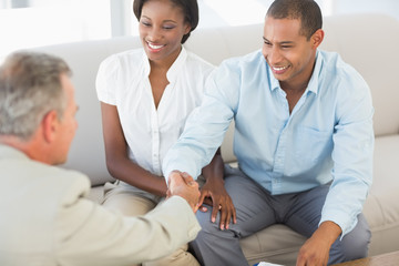 Young couple shaking hands with salesman on the sofa