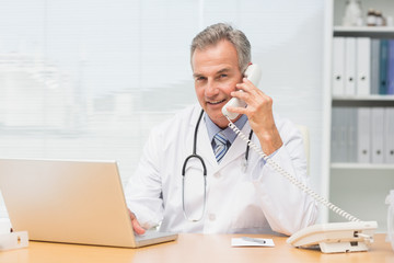 Smiling doctor using laptop and talking on phone at desk