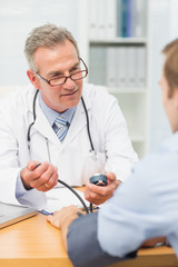 Smiling mature doctor taking his patients blood pressure