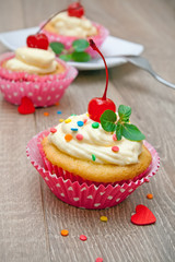 Berry cupcakes on the wooden background