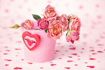 Pink roses in a flower pot decorated with a heart .