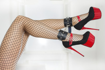 Legs wearing fishnet stockings, ankle cuffs and extreme high hee