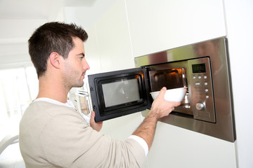 Man heating food in microwave