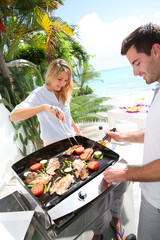 Cheerful couple preparing grilled food on barbecue