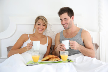 Cheerful young couple having breakfast in bed