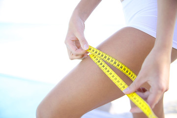 Closeup of woman measuring leg line