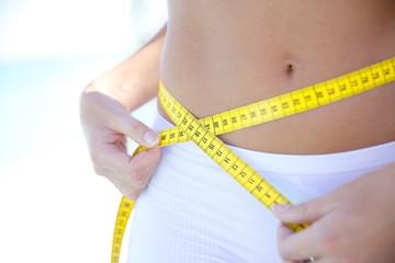 Closeup of woman measuring waist line